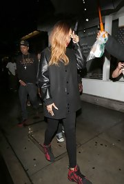 Rihanna rocked a black snap button coat with leather sleeves for an outing in LA.