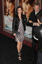 Jennifer Connelly paired a floral print dress and leather jacket with a leather wristlet by Balenciaga. The gray leather accentuated her boldly strappy sandals.