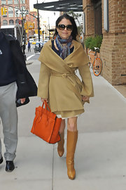 Bethenny Frankel stepped out in NYC wearing a tan wool coat and carrying a vibrant handbag.