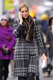 Kelly wears a fur scarf with her plaid coat on the set of 'Gossip Girl.'