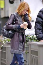 Blake Lively mixed shades of purple on set in a purple leather coat and grape quilted purse.