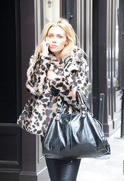Abbey Clancy accessorized her faux leopard print coat with a crackled leather tote.