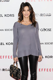Gina Gershon contrasted her edgy outfit with an ultra-feminine single-strap lace tote.