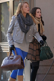 Black wore a cozy knitted grey infinity scarf as part of her on set wardrobe.