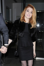 Nicola wears a little black dress with a chic ruffle and cropped fur jacket.
