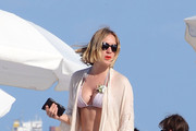 Chloe Sevigny shows of her tanned and toned beach body while celebrating the New Year in South Beach, Florida. Sevigny wore a pink and grey string bikini as she spent the day tanning, swimming and snacking with friends at a Miami beach. The