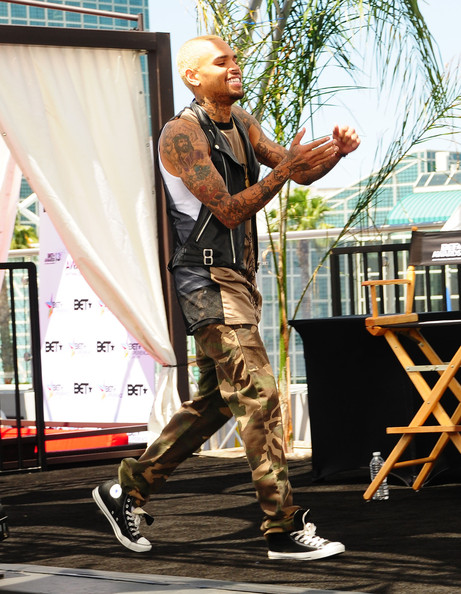 Chris Brown walked confidently onstage while wearing a pair of skinny camo pants.