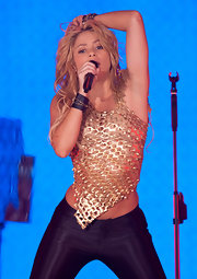 Shakira shakes it up on stage in a fierce gold top and tight black pants.