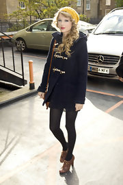 Taylor paired her navy blue pea coat with an on-trend pair of perforated high heel oxfords.