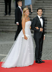 Princess Madeleine contrasted the stark white of her gown with a silver envelope clutch as she attended the wedding of Crown Princess Victoria and Daniel Wrestling.