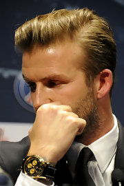 David Beckham accessorized his look with a black and gold watch.
