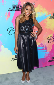 Angela Simmons rocked a deep navy blue leather dress with a flowing skirt and a geometric embellished bodice.