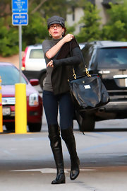 Teri Hatcher carried a black leather tote with gold hardware. The boxy oversized bag matched Teri's over-the-knee flat boots.