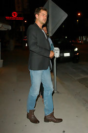 The actor wore worn leather ankle boots with bootcut jeans ans a black blazer.