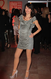 Karina dons a silver ruched cocktail dress with short butterfly sleeves and suede insets at the AIDS benefit gala.
