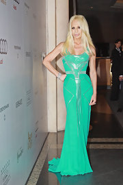 Donatella Versace strikes a pose in one of her latest creations. This teal geometric dress showed off her silhouette with complete ease.