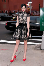 Krysten Ritter paired vibrant cherry red pumps with her black lace overlay dress at the premiere of 'Don't Trust the B---- in Apartment 23.'