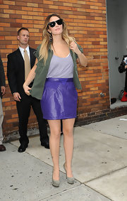 Drew Barrymore paired her purple mini skirt with an army green shirt and platform pumps.