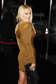 Charlotte Ross added drama to her mustard mini dress with a feather and bead embellished clutch.
