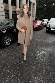 Anna Kendrick kept it classic with this red hard-case clutch and tan wool coat combo during London Fashion Week.