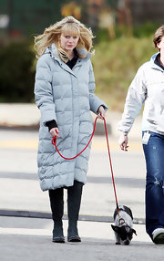 Emma wears a long powder blue down jacket for walking her pup.