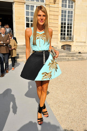 Anna dello Russo cut a shapely silhoutte in a turquoise and black Fausto Puglisi dress with tropical-inspired beading during the Christian Dior fashion show.