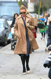 Stella wears a tan trench camel trench over a blue print dress while out in London.