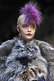 Cara Delevingne looked high-fashion wearing purple lipstick at the Fendi fashion show.