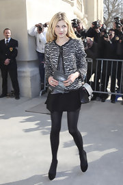 Clemence looked like classic Chanel at the Paris fashion show wearing a tweed jacket and black skirt.