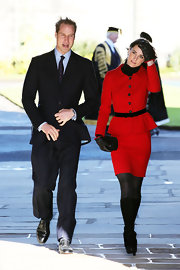 Kate Middleton looked sophisticated in a stunning red suit with a peplum jacket with a black velvet belt.