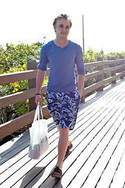 Tom wears blue floral board shorts for his beach trip.