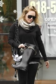 Hilary looks comfortable in her stylish black ensemble with black shades. She adds a touch of gray to give the look personality.