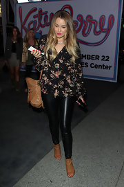 Lauren Conrad opted for a relaxed feminine look at the Katy Perry concert in a black floral print blouse. She teamed the top with faux leather leggings.