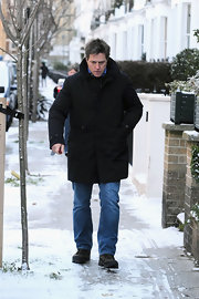 Hugh stays warm in the snow with a thick black winter coat.