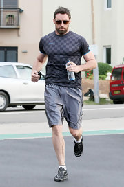 Hugh wears a tight t-shirt while going for a run.