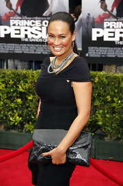 Actress Tia Carrere paired her curve hugging black dress with layered chain link necklaces.
