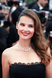 Virginie Ledoyen added a touch of old Hollywood glamour to her look with long side-swept waves and bold red lipstick.