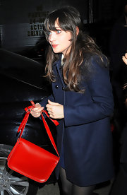 Zooey Deschanel punched up her look with a bright red leather purse and matching lip gloss.