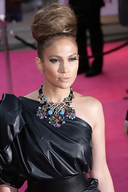 "Jennifer Lopez showed off her one-shoulder dress and dazzling necklace that came straight from the runway. Her ""Brace Breastplate"" necklace brought her look to life."