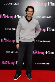 Layering this light gray V-neck sweater over a black shirt gave Gilles a refined yet casual edge.