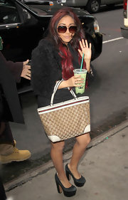 Nicole 'Snookie' Polizzi accented her provocative streetwear with a classic Gucci purse.