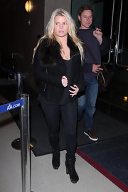 Jessica Simpson hit LAX in black suede lace-up boots with wooden platforms.