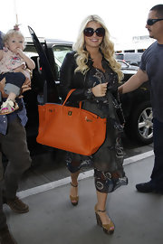 Jessica Simpson orange tote brought some summery color to the star's ensemble.