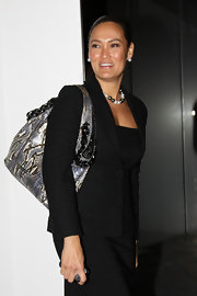 A snakeskin tote added some boldness to Tia Carrere's basic black skirt suit.