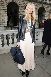 Poppy Delavigne accented her tough twist on boho-chic style with a black backpack.