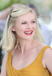 Kirsten pinned her hair back with a gold barrette while attending the photo call for 'Melancholia'.