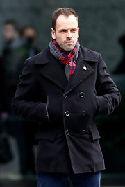 Jonny Lee Miller brought a little color to his all dark look with this red checkered scarf.