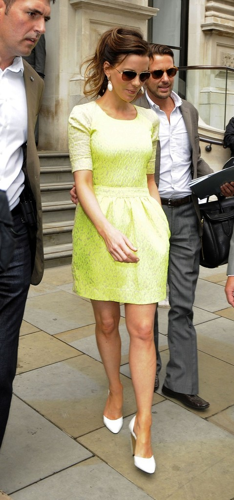 "Kate Beckinsale is helped down the stairs as she leaves the Corinthia Hotel to head to the premiere of ""Total Recall"" in London. The ""Underworld"" actress wore a bright yellow dress and white heels as she walked down the steps holding onto the arm of an assistant."
