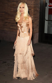 Donatella wears a luxurious bisque fringe evening gown. This glamorous number is designer by--who other--Versace.