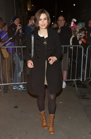Keira Knightley left the theater in lace up cognac leather boots, which she wore over a pair of slightly sheer black tights.